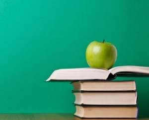 apple on pile of books, isolated on green background